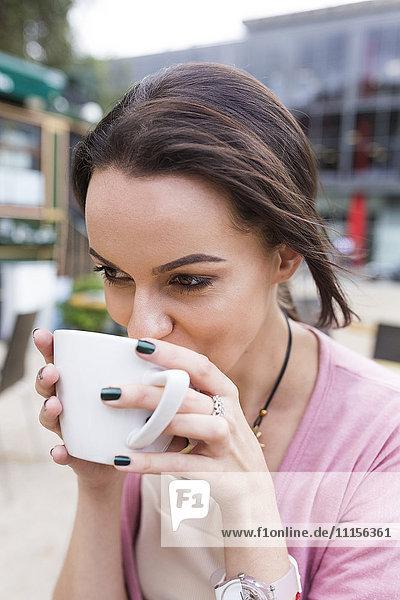 Junge Frau trinkt Cappuccino