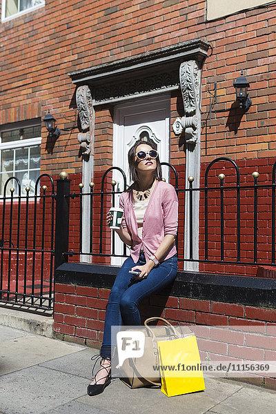 Irland  Dublin  Frau mit Einkaufstüten und Kaffee zum Sonnenbaden