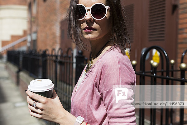 Modische junge Frau mit Kaffee zum Mitnehmen mit rosa Sonnenbrille und Strickjacke