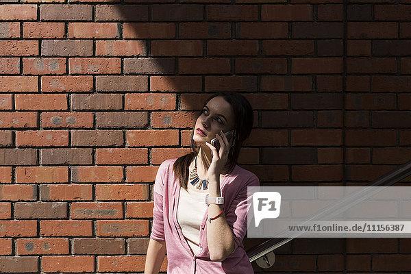 Junge Frau am Telefon vor der Backsteinmauer