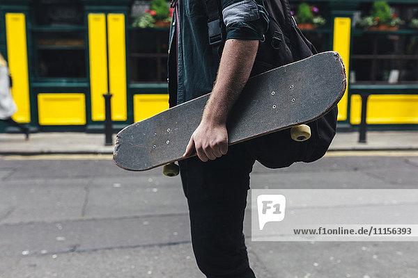 Junger Mann mit Skateboard und Rucksack  Teilansicht
