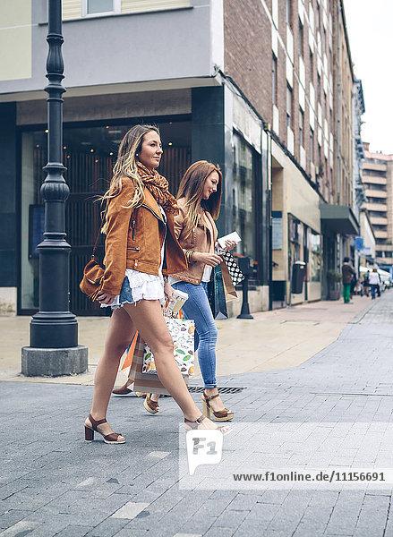 Zwei Frauen mit Einkaufstaschen  die in der Stadt spazieren gehen.