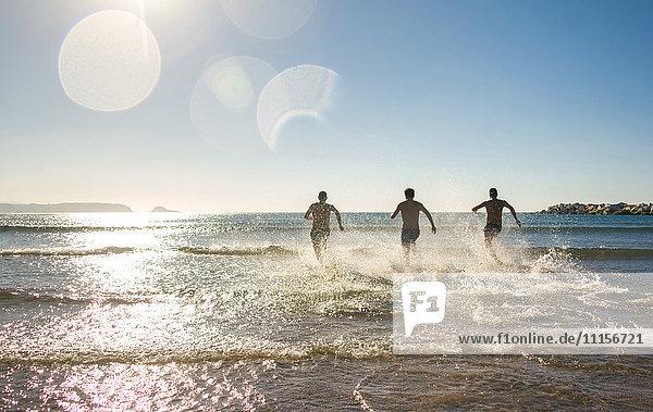 Freunde laufen und springen ins Meer.