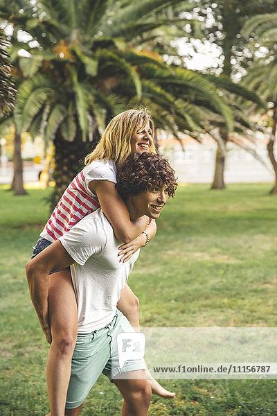 Junger Mann  der seine Freundin im Park mitnimmt.