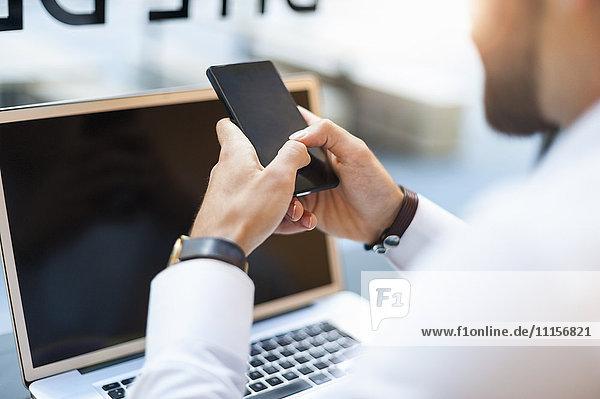Nahaufnahme eines Geschäftsmannes mit Handy und Laptop in einem Cafe