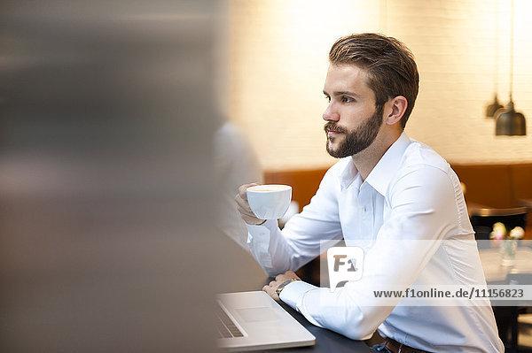 Geschäftsmann mit Kaffee und Laptop im Cafe