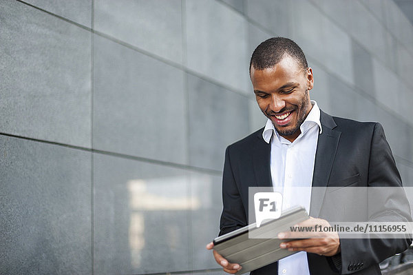 Lächelnder Geschäftsmann mit Tablette