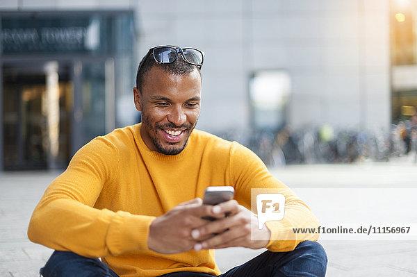 Lächelnder Mann mit gelbem Pullover beim Blick aufs Handy