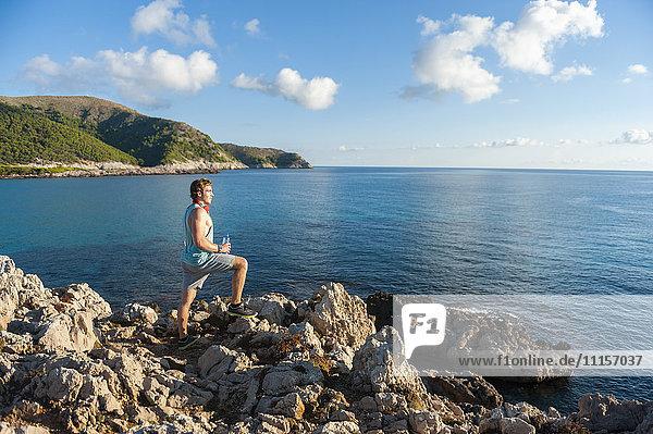Spanien  Mallorca  Sportler am Morgen an der Felsenküste stehend