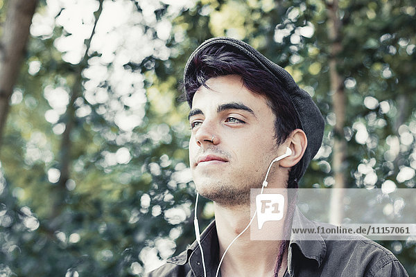 Portrait of smiling young man with cap listening music with earphones