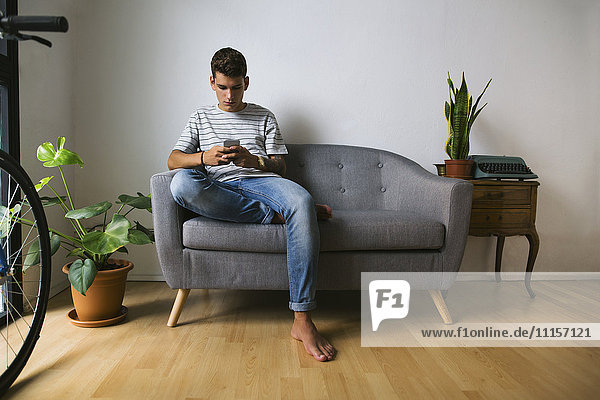 Teenage boy sitting on couch at home looking at cell phone