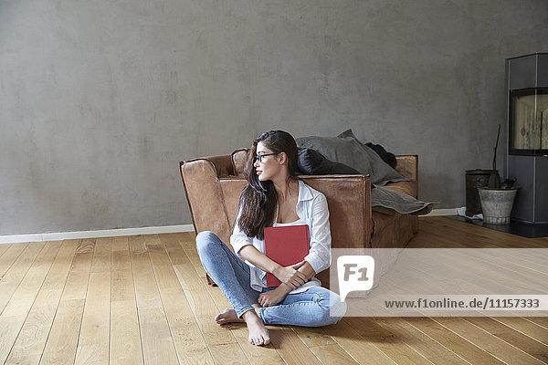 Junge Frau sitzend mit Buch auf Holzboden zu Hause