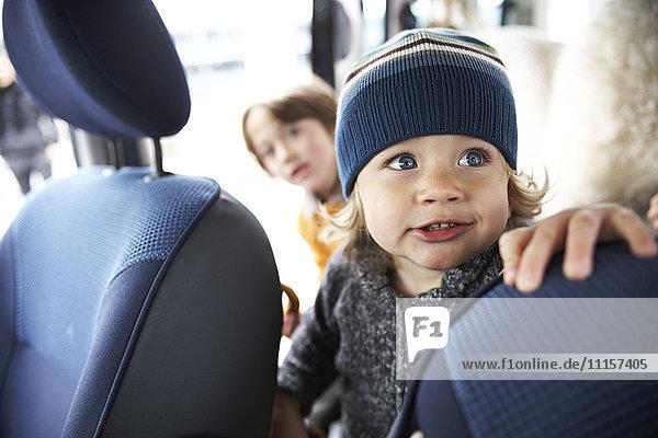 Kleiner Junge sitzend im Auto mit Brüdern