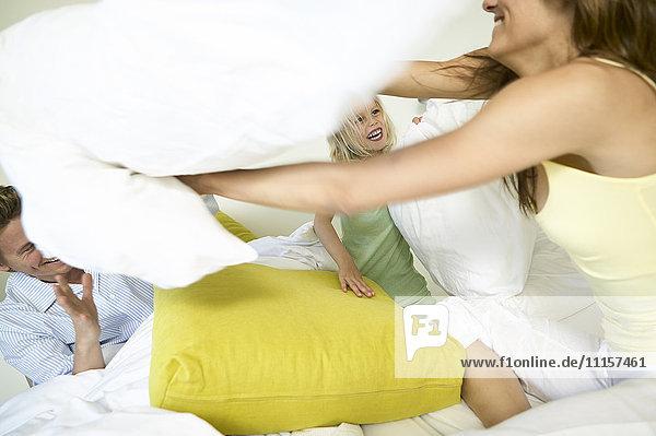 Familie mit Kissenschlacht im Bett