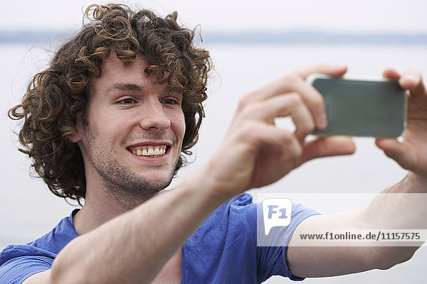 Smiling young man taking a selfie at a lake