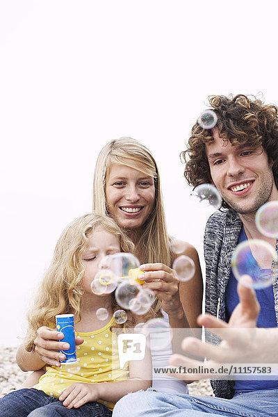 Eltern mit Tochter  die Seifenblasen bläst.