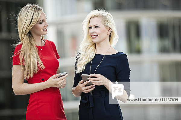 Two fashionable businesswomen with smartphones