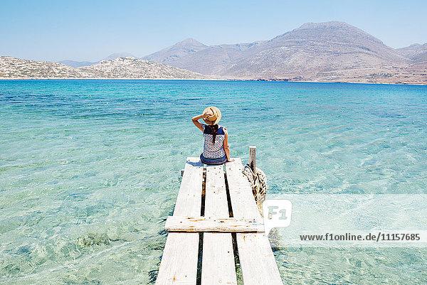 Griechenland  Kykladen  Amorgos  Frau am Rande eines hölzernen Piers  Insel Nikouria