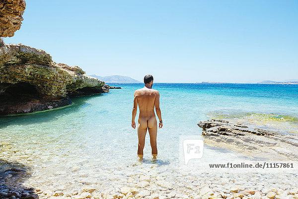Griechenland  Koufonissi  Nackter Mann steht im klaren Wasser der Ägäis