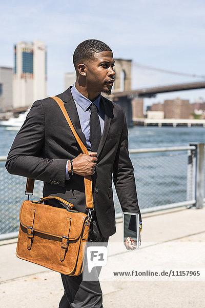 USA  Brooklyn  wandelnder Geschäftsmann mit Aktentasche und Mini-Tablette
