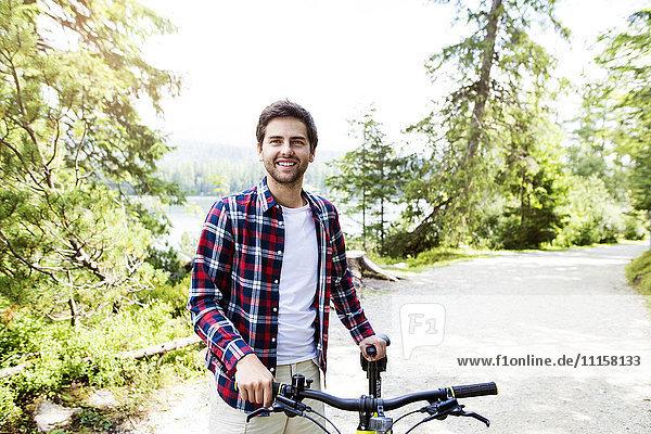 Junger Mann auf dem Fahrrad in der Natur