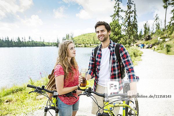 Junges Paar macht eine Pause auf einer Fahrradtour