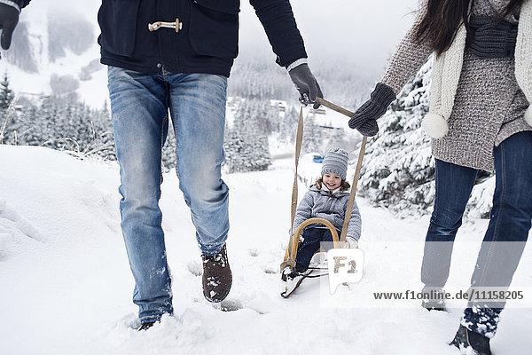 Familie mit Schlitten in der Winterlandschaft