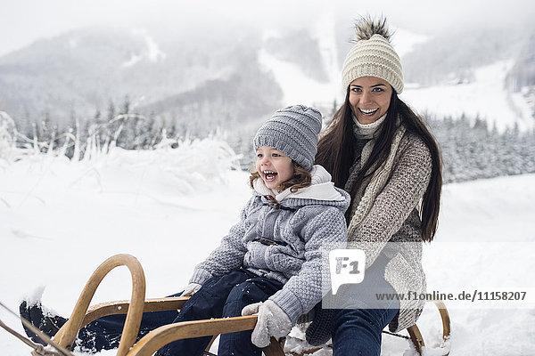 Glückliche Mutter mit Tochter auf Schlitten in Winterlandschaft