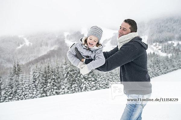 Vater spielt mit Tochter in der Winterlandschaft