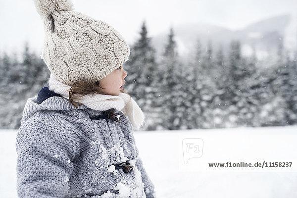 Mädchen in der Winterlandschaft schaut sich um