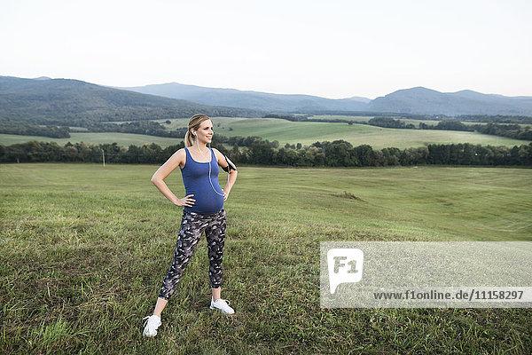 Schwangere Frau steht in ländlicher Landschaft und macht eine Pause vom Joggen.