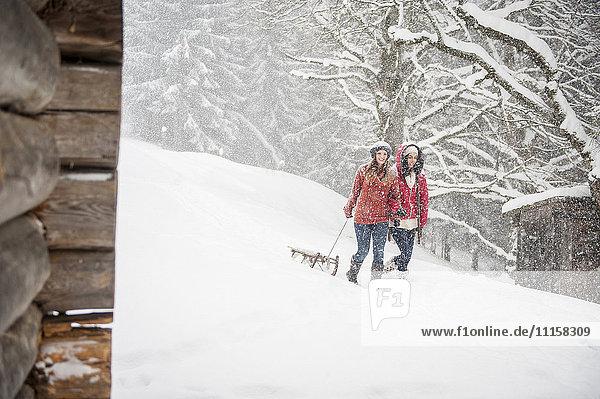 Zwei junge Frauen mit Schlitten bei starkem Schneefall