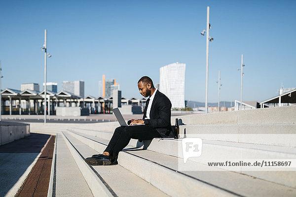 Geschäftsmann auf der Treppe sitzend mit Bierflasche und Laptop