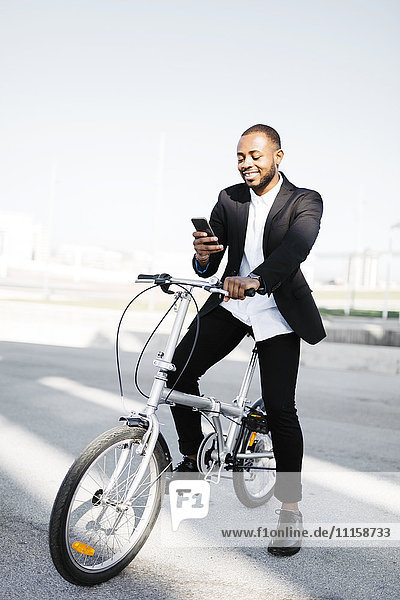 Lächelnder Geschäftsmann mit Fahrrad beim Blick aufs Handy