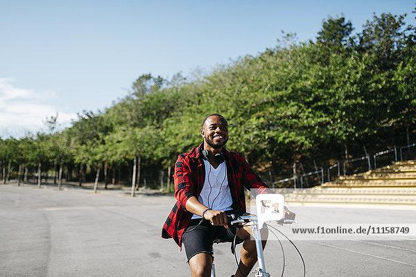 Lächelnder Mann auf dem Fahrrad durch einen Park