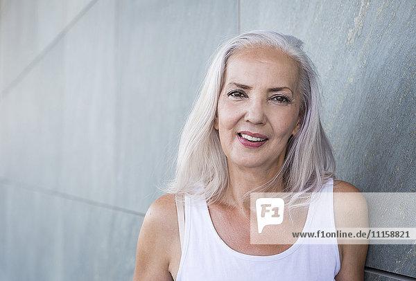 Porträt einer lächelnden Frau mit grauem Haar an der Wand lehnend