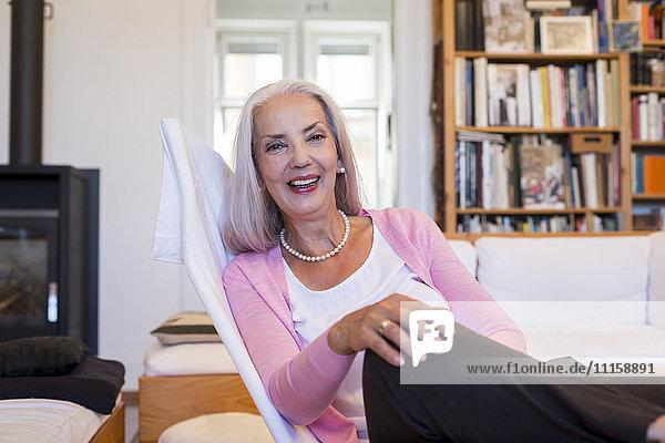 Lachende Frau sitzend im Sessel zu Hause