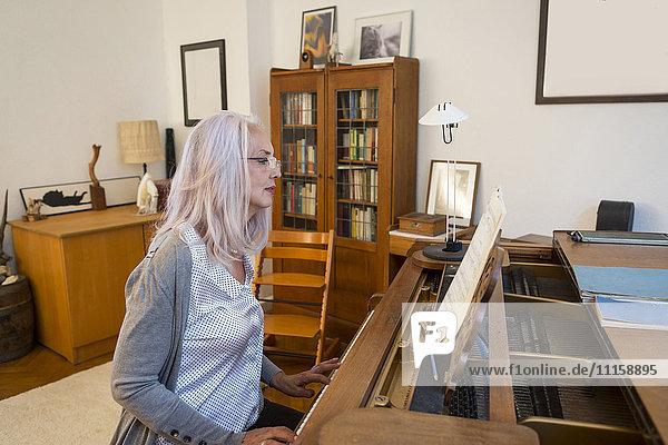 Frau spielt zu Hause Klavier