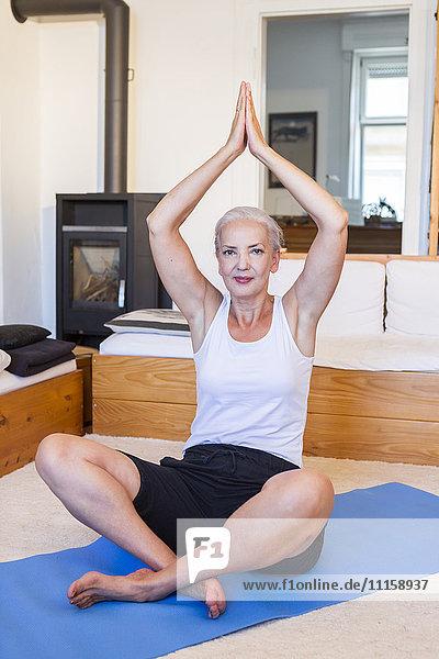 Frau  die zu Hause Yoga praktiziert