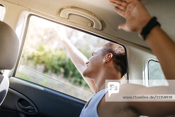 Glücklicher junger Mann  der sich aus dem Autofenster lehnt.