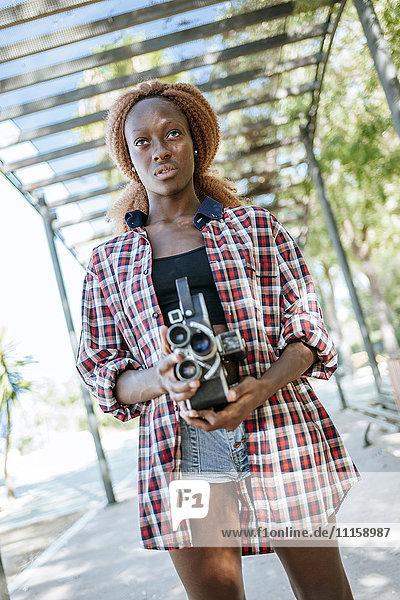 Junge Frau mit altmodischer Kamera