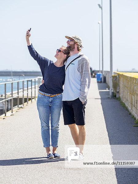 Frankreich  Bretagne  Finistere  glückliches junges Paar  das sich mit einem Smartphone im Hafen vergnügt.