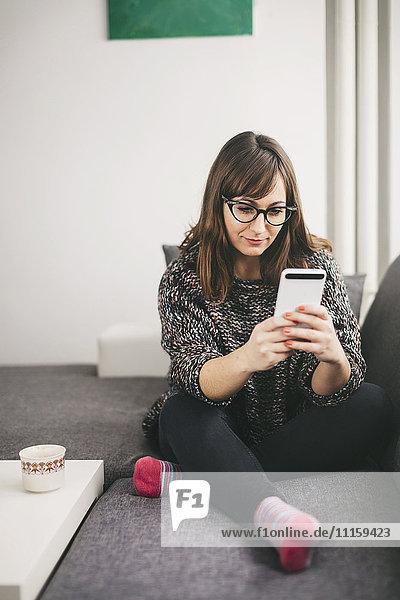 Junge Frau entspannt auf der Couch mit Blick auf ihr Smartphone