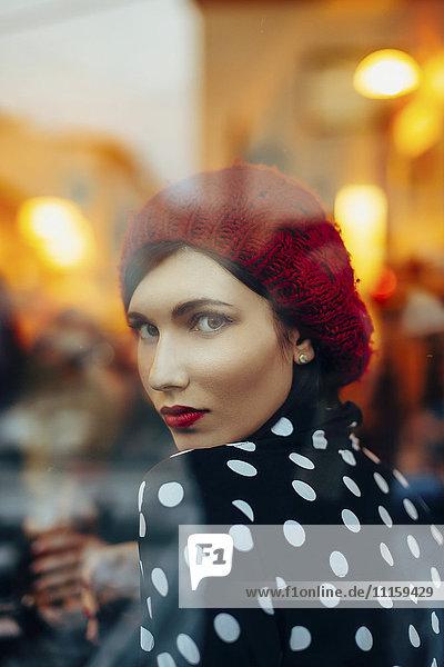 Porträt einer jungen Frau mit rotem Hut  die abends durch das Fenster eines Pubs schaut.