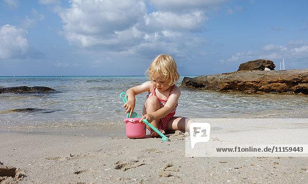 Kleines Mädchen spielt am Strand
