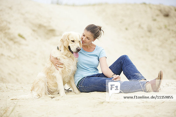 Junge Frau mit Hund im Sand