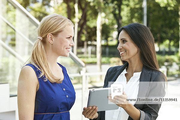 Zwei lächelnde Frauen mit digitalem Tablett im Freien
