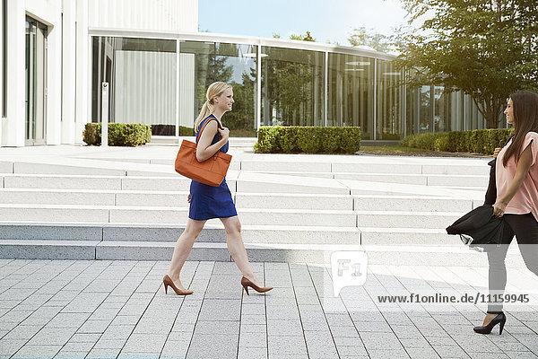 Zwei Frauen vor einem modernen Bürogebäude