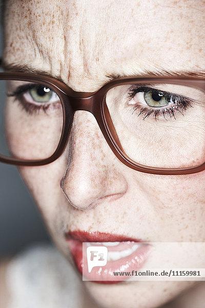 Nahaufnahme des wütenden Frauengesichtes mit Sommersprossen und Brille