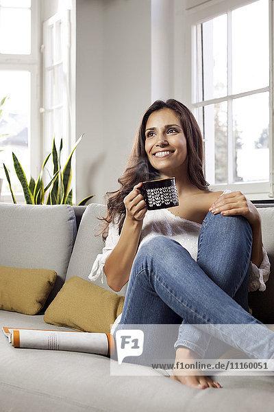 Lächelnde Frau entspannt auf der Couch mit einem Becher
